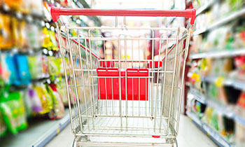 Supermarket interior, empty red shopping cart.
